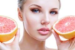 Jonge vrouw met grapefruit in handen Royalty-vrije Stock Afbeeldingen