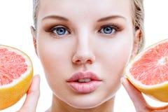 Jonge vrouw met grapefruit in handen Stock Afbeelding