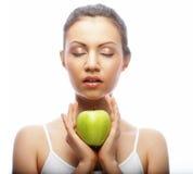 Jonge vrouw met groene die appel op witte achtergrond wordt geïsoleerd Stock Fotografie