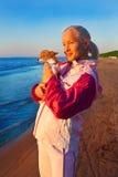 Jonge vrouw met haar hond op een strand Royalty-vrije Stock Afbeeldingen