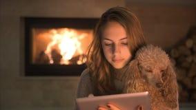 Jonge vrouw met haar hondzitting op vloer en het gebruiken van tablet