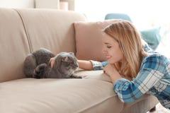 Jonge vrouw met haar huisdierenkat thuis royalty-vrije stock foto