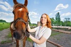 Jonge vrouw met haar paard naast bijlageomheining Royalty-vrije Stock Foto