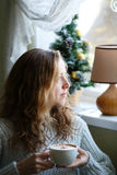 Jonge vrouw met in hand zitting van de koffiekop dichtbij het venster Royalty-vrije Stock Foto