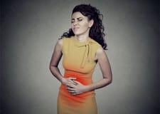 Jonge vrouw met handen op maag die slechte pijnenpijn hebben royalty-vrije stock afbeelding