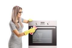 Jonge vrouw met handschoenen die een oven schoonmaken royalty-vrije stock fotografie