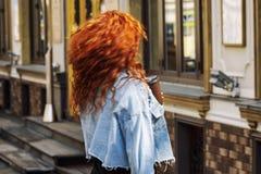 Jonge vrouw met helder lang rood haar op een stadsstraat royalty-vrije stock foto's