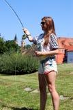 Jonge vrouw met hengel op een rivier in Duitsland Stock Foto's