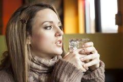 Jonge Vrouw met het Mooie Blauwe Drinkwater van Ogen stock afbeelding