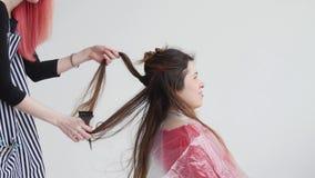 Jonge vrouw met het rode haar van haarbesnoeiingen aan vrouw bij de kapper stock footage