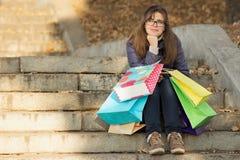 Jonge vrouw met het winkelen zakken op de stappen van pakketten royalty-vrije stock afbeeldingen