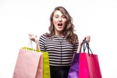 Jonge vrouw met het winkelen zakken over witte en achtergrond die gillen benieuwd zijn royalty-vrije stock afbeeldingen