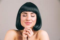 Jonge vrouw met het zwarte haar stellen op camera Het dromerige aardige model houdt ogen gesloten samen en handen Glimlach Rust e royalty-vrije stock foto