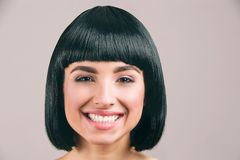 Jonge vrouw met het zwarte haar stellen op camera Vrolijke aardige modelglimlach Zwart loodjeskapsel Ge?soleerdi op lichte achter royalty-vrije stock afbeelding