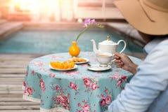 Jonge vrouw met hoed het drinken thee met koekje en oranje fruit royalty-vrije stock afbeelding