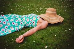 Jonge vrouw met hoed het ontspannen in park stock fotografie