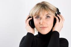 Jonge vrouw met hoofdtelefoon op grijs Stock Afbeelding