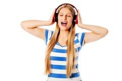 Jonge vrouw met hoofdtelefoons die die en aan muziek luisteren zingen, op wit wordt geïsoleerd Royalty-vrije Stock Afbeelding