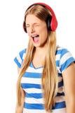 Jonge vrouw met hoofdtelefoons die die en aan muziek luisteren zingen, op wit wordt geïsoleerd Stock Foto's