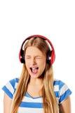 Jonge vrouw met hoofdtelefoons die die en aan muziek luisteren zingen, op wit wordt geïsoleerd Stock Afbeeldingen