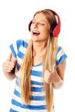 Jonge vrouw met hoofdtelefoons die die en aan muziek luisteren zingen, op wit wordt geïsoleerd Royalty-vrije Stock Afbeeldingen
