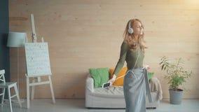 Jonge vrouw met hoofdtelefoons die en aan muziek thuis dansen luisteren stock videobeelden