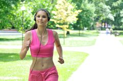Jonge vrouw met hoofdtelefoons die in park lopen Stock Fotografie