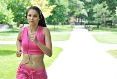Jonge vrouw met hoofdtelefoons het lopen Royalty-vrije Stock Afbeeldingen