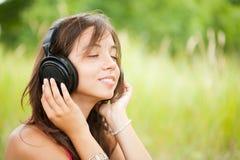 Jonge vrouw met hoofdtelefoons openlucht Stock Foto's