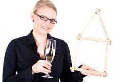 Jonge vrouw met huissymbool en champagneglas Stock Foto's