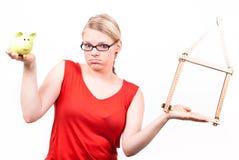 Jonge vrouw met huissymbool en spaarvarken Royalty-vrije Stock Fotografie