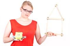 Jonge vrouw met huissymbool en spaarvarken Stock Fotografie