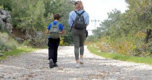 Jonge vrouw met jongen het lopen op de weg stock footage