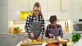 Jonge vrouw met jongens scherpe groenten stock footage