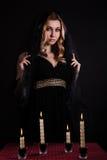 Jonge vrouw met kaarsen in duisternis Stock Foto's