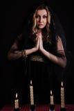 Jonge vrouw met kaarsen in duisternis Royalty-vrije Stock Afbeelding