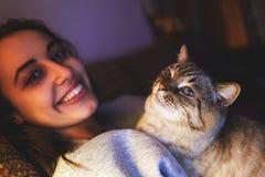 Jonge vrouw met kat bij avond stock afbeeldingen