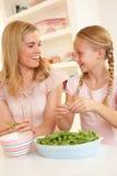 Jonge vrouw met kind verdelende erwt in keuken Stock Fotografie