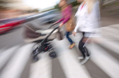 Jonge vrouw met kleine kinderen en een kinderwagen die onderaan stre lopen Royalty-vrije Stock Fotografie