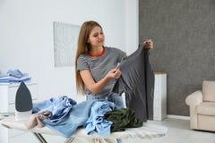 Jonge vrouw met kleren dichtbij strijkplank stock fotografie