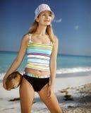 Jonge vrouw met kokosnoot op het strand Stock Afbeelding