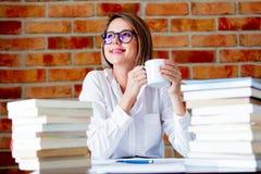 Jonge vrouw met kop koffie en boeken royalty-vrije stock foto