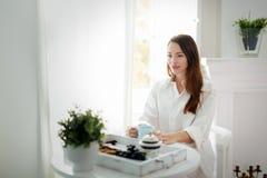 Jonge vrouw met kop van koffiezitting bij lijst stock afbeeldingen