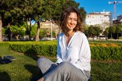 Jonge vrouw met krullend haar die in park rusten Stock Foto