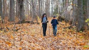 Jonge vrouw met krullend haar en een jongen op Skandinavische gang stock videobeelden