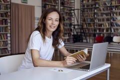 Jonge vrouw met lang haar die aan laptop op mede-werkt kantoor of bibliotheek, boekenrek erachter werken Greepboek in handen Onde stock foto