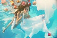 Jonge vrouw met lang haar onder water stock foto