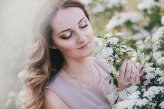 Jonge vrouw met lang mooi haar in chiffonkleding het stellen met lilacintuin met witte bloemen Stock Afbeeldingen