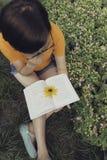 Jonge vrouw met lange haarzitting in de lezing van de vensterzetel Stock Foto