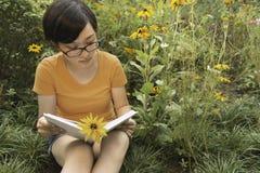 Jonge vrouw met lange haarzitting in de lezing van de vensterzetel stock afbeelding